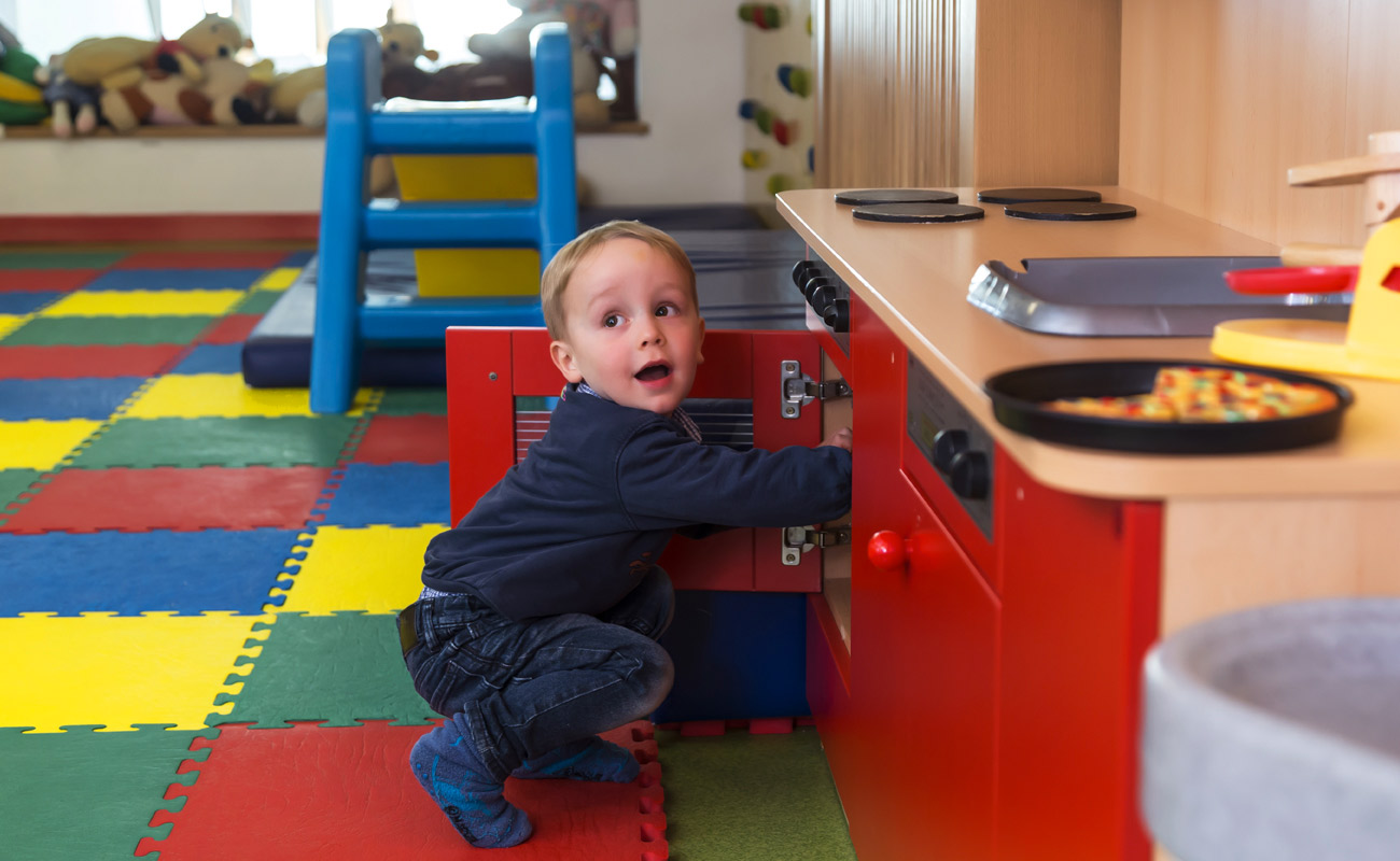 Child plays with the kitchen in the game room of Hotel Ambiez