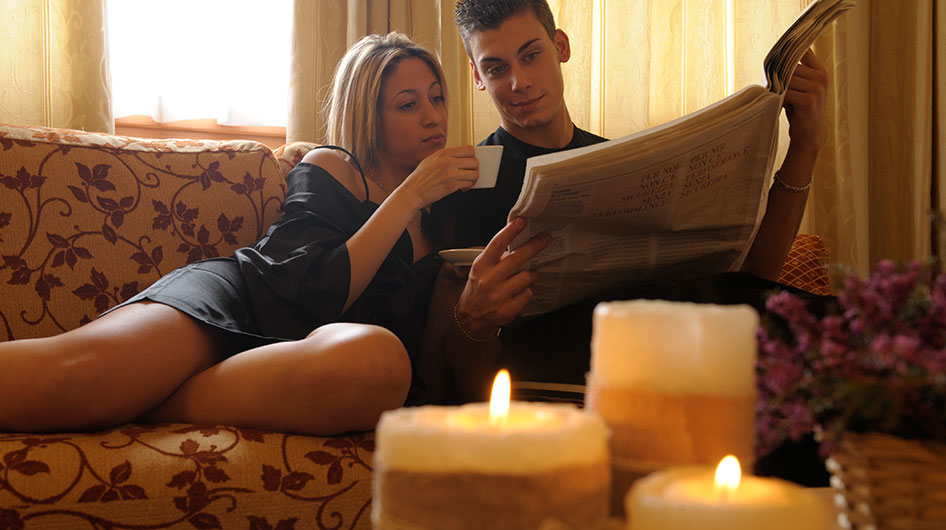 A couple relaxes on the couch reading a newspaper and drinking tea